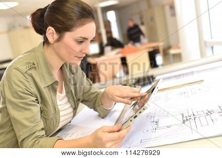 Woman architect working on drawing table in office