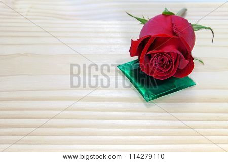 Red Rose And Condom On Wooden Table, Love Concept For Valentines Day