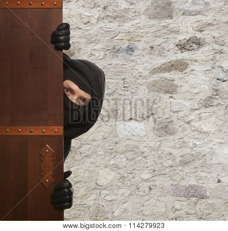 Ninja. Robber hiding behind a wooden doors with space for text