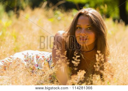 A young and attractive girl in beautiful summer dress middle of sunny meadows.
