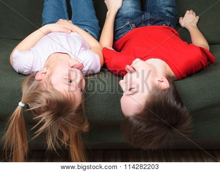 Brother and sister  wearing casual clothes  laying on a green sofa at home stick out tongues teasing each other