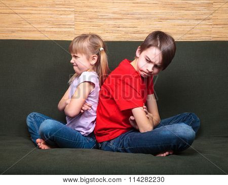 Brother and sister  wearing casual clothes  sitting on a green sofa at home arms crossed back to back angry with each other