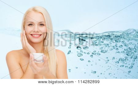 woman applying moisturizing cream to her face skin