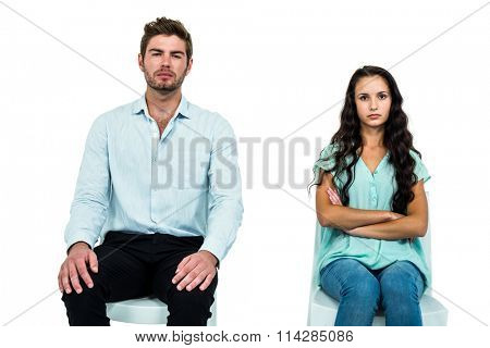 Couple sitting on chairs not talking after argument over white background