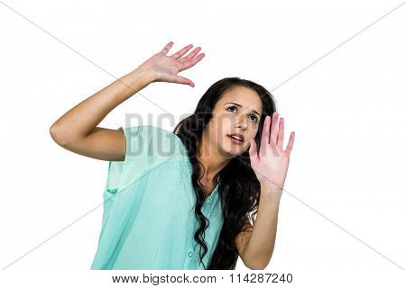 Scared woman raising hands on white screen