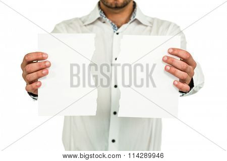 Standing man showing torn papers while standing on white background