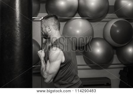 Muscular man in the gym. The man in boxing gloves, hit a punching bag, exercise
