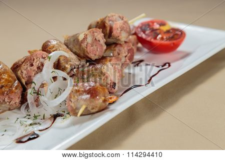 Tasty sausages with sauce and vegetables on a white plate