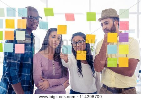 Creative team discussing over adhesive notes on glass in office