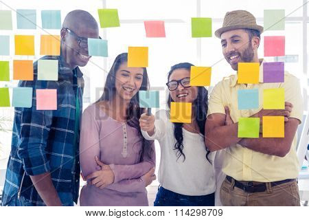 Happy creative team discussing over adhesive notes on glass in office