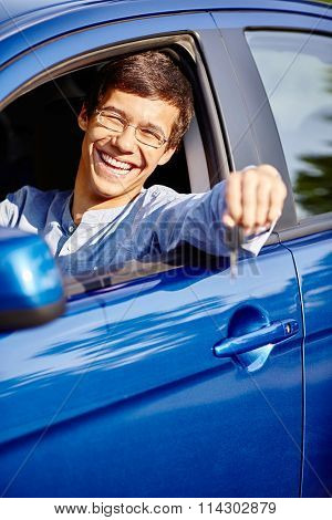 Young hispanic man wearing glasses and jeans shirt sitting behind wheel and holding out his car keys through window and smiling - new drivers concept