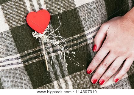 Red Heart On Stick With Woman Hand With Red Manicure On Blanket Background