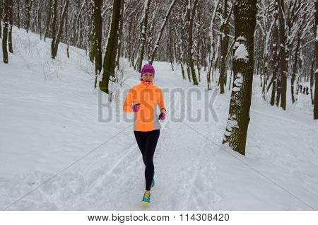 Winter running in forest: happy woman runner jogging in snow, outdoor sport and fitness concept