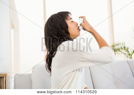Woman using her inhaler on the couch at home