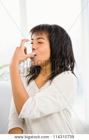 Pretty woman using inhaler on couch at home in living room