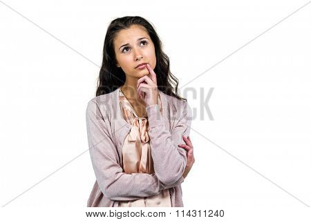 Thoughtful woman looking away with finger on mouth over white background