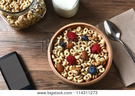 High angle view of a bowl of breakfast cereal with blueberries, raspberries and nuts. A bottle of milk and cell phone are also on the rustic wood table.