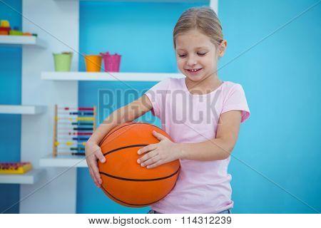 Cute girl standing holding a basket ball