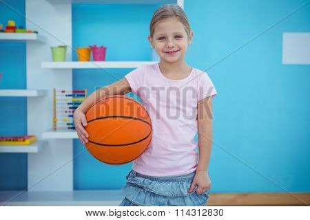 Cute girl holding basket ball and smiling at the camera