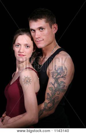 Tattooed Couple In Tank Tops