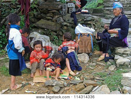 children and their mother are sitting outdoor in Sa Pa, Vietnam