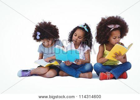 Cute girls sitting on the floor reading books on white screen