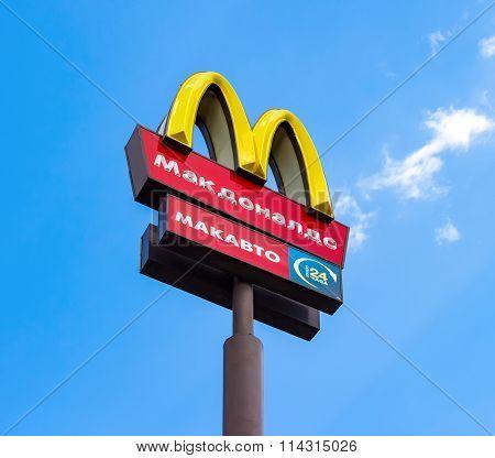 Mcdonald's Logo On A Pole Against The Blue Sky
