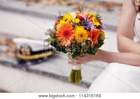 Closeup of bride's hands holding bouquet with military hat out of focus in background