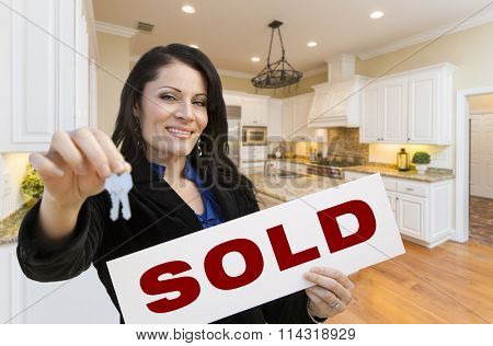 Pretty Hispanic Woman In Kitchen Holding House Keys and Sold Sign.