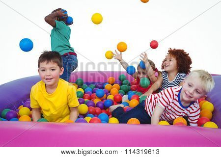 Cute smiling kids in sponge ball pool throwing balls