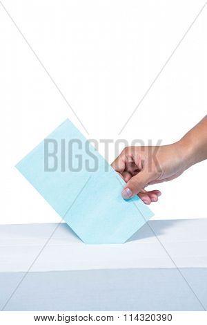 Businesswoman putting ballot in vote box on white background