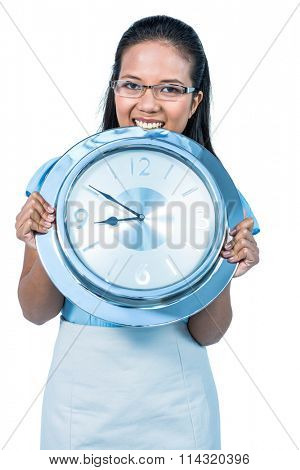 Delighted businesswoman holding a clock against white background