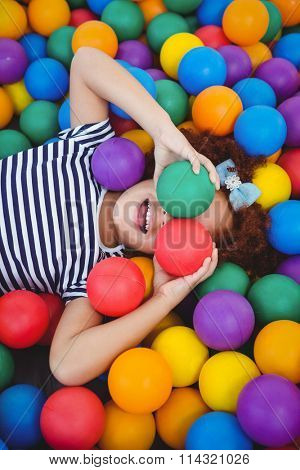 Cute smiling girl in sponge ball pool covering eyes with balls