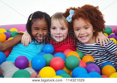 Cute smiling girls in sponge ball pool hugging and looking at the camera