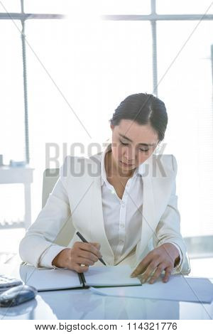 Businesswoman writing on diary on desk in her office