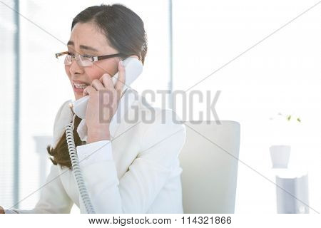 Anxious businesswoman using landline at her desk