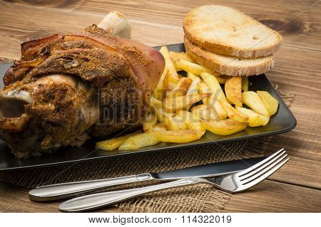 Roasted pork knuckle with potatoes on black plate on wooden background.