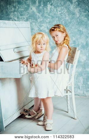 Two beautiful sisters in white dresses playing the piano. Music and art concept. Vintage style.