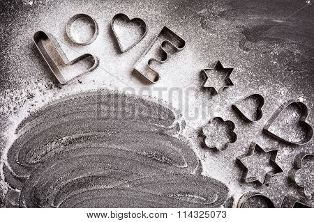 Love shaped cookie cutters and flour on black background