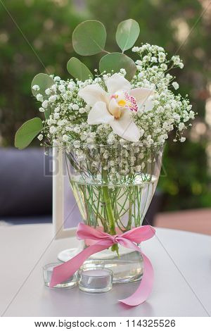 Wedding Table Decoration. Beautiful flowers on table in wedding day. Table decor with flowers table numbers and candles.