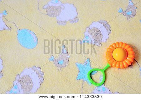 Baby rattle on beige background