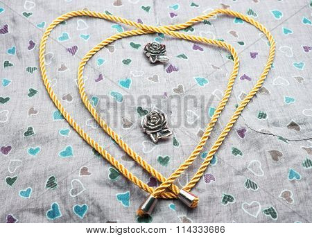 Metal roses and golden rope with heart shape on fabric background with colorful heart pattern