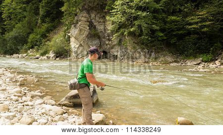 Fishing. Fishing in the highlands. Fisherman on the shore of a mountain, fast river