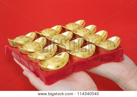 Hand Giveing Gold Ingot To Someone For Chinese New Year Celebration On Red Background