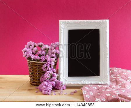 White Vintage Photo Frame With Sweet Statice Flower In Basket  On Red Pink Background And Wooden Tab