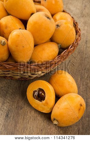 Loquat Medlar Fruit On Wooden Background.