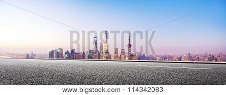 empty asphalt road and cityscape in illuminated blue sky at dawn
