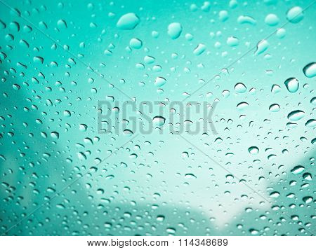 Raindrops On Car's Glass With Blurry Cloudy Sky In Village. Green Color Tone