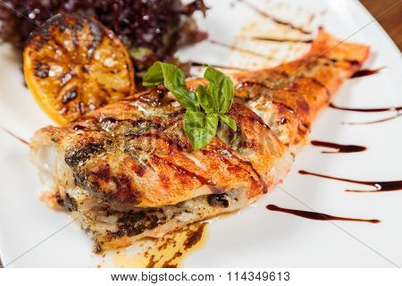 Grilled fish with grilled vegetables and sauce. Tasty Mediterranean food