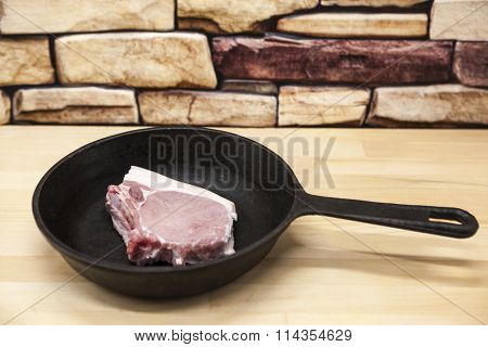 A piece of delicious fresh raw pork close-up on a cast iron skillet on the table rustic kitchen.